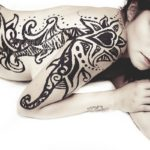 woman with tattoo on back and arm lying on stomach