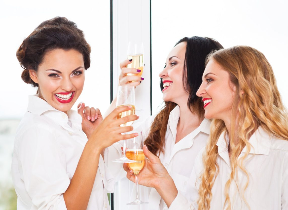 women holding champagne glasses and smiling