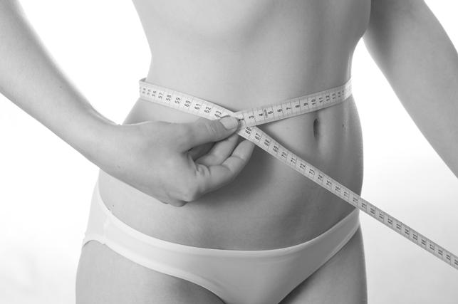 Woman measuring tape around waist