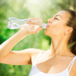 woman drinking water out of bottle